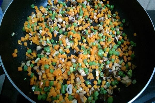 Cho hết cà rốt, đậu Hà Lan, tôm, mực vào xào cho chín