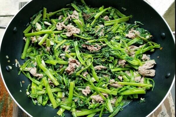 Khi thấy rau muống đã vừa chín tới, các bạn cho thịt bò đã xào vào lại chảo