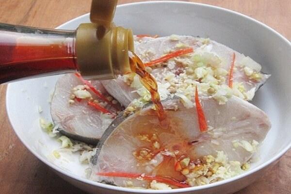 Bạn cắt cá bớp thành khúc vừa ăn rồi ướp trong bát tô