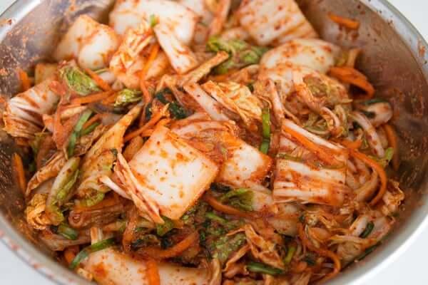 Thêm hành lá cắt lát và bột ớt vào bắp cải, trộn hốn hợp lên