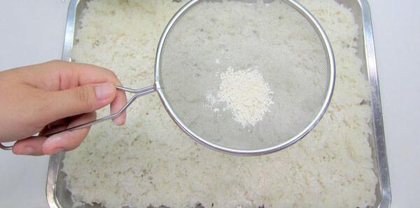 Rắc xong, bạn lật mặt kia của cơm lên và rắc nốt phần còn lại.