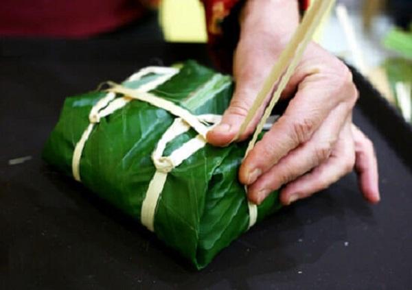 Sau khi buộc xong, dùng tay ấn 4 phía của bánh để bánh được chặt
