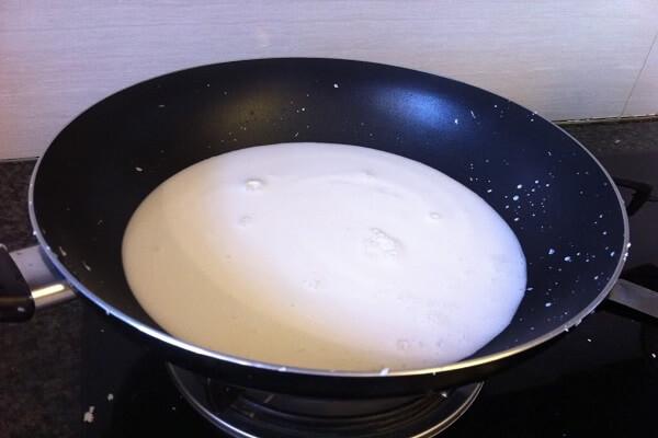 Cho 2 loại nước cốt dừa vào nồi, đặt nồi lên bếp với lửa vừa và đun