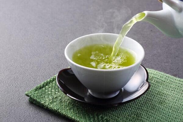 Rót trà ra một cốc nhỏ, để cặn lắng