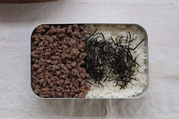 Cho cơm vào hộp chuẩn bị sẵn.