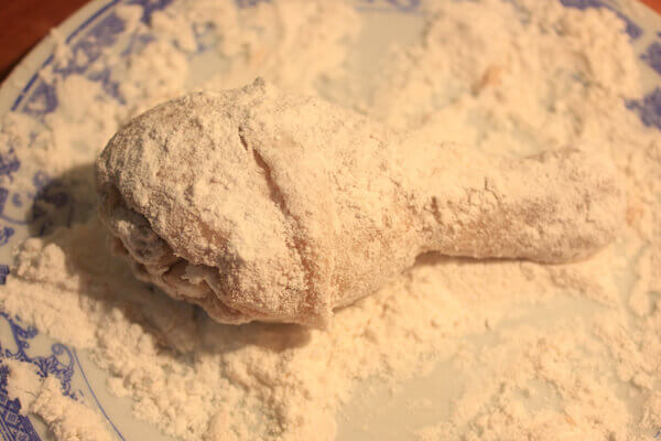 Cho gà vào tô to, cho bột aji quick vào, sau đó trộn đều cho bột bám đều trên đùi gà.