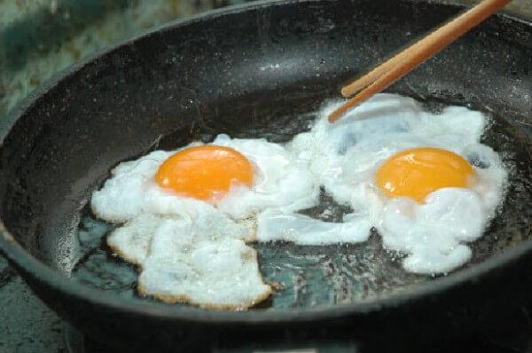 Ốp trứng trong chảo dầu, đun lửa nhỏ để trứng chín đều