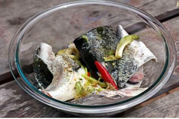 Đầu cá hồi mua về rửa sạch, ướp với gia vị khoảng 30 phút.