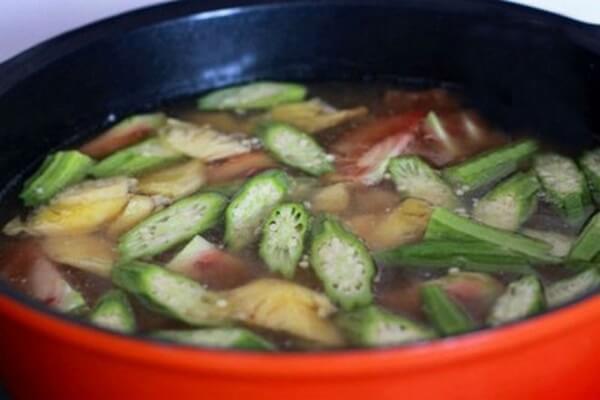 Khi canh sôi cho thơm, cà chua, đậu bắp vào nấu.