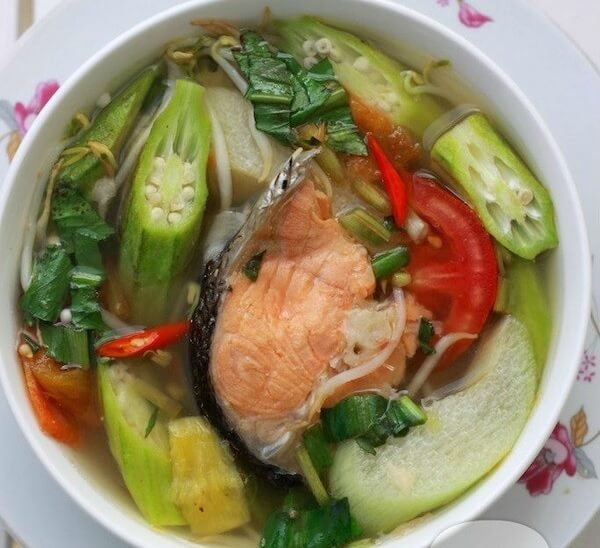 Múc canh chua đầu cá hồi ra tô, rắc rau om ngò gai lên trên mặt.