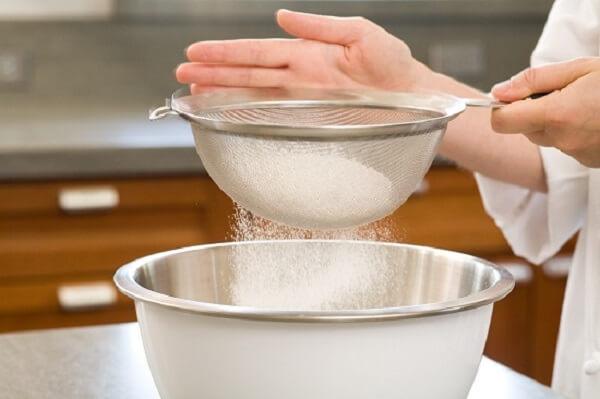 Rây bột mì vào hỗn hợp làm vỏ bánh sầu riêng