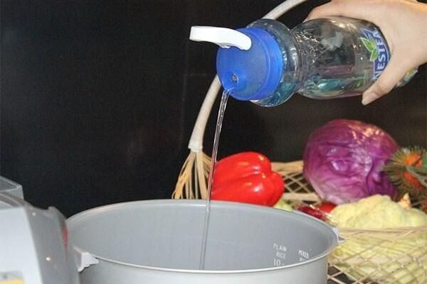 Đổ nước lọc vào nồi cơm điện và phủ tấm giấy nướng bánh đã phết bơ nên trên