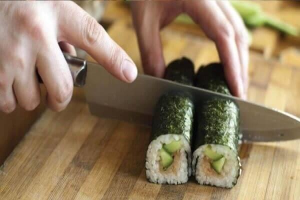 Các bạn cho cơm cuộn ra một chiếc đĩa sau đó cắt thành từng lát vừa ăn