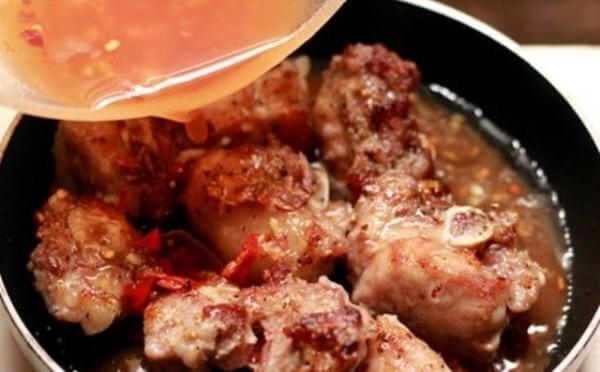 Đổ nước sốt chua ngọt vào chảo sườn xào tiếp cho chín mềm