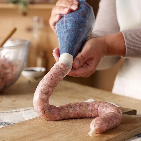 Dùng một chiếc phễu nhỏ để nhồi phần thịt xay đã trộn vào lòng.